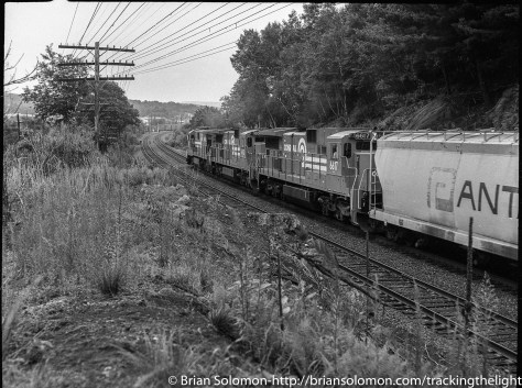 Conrail's C30-7A and C32-8 diesels roll east with tonnage at milepost 84 in Monson, Massachusetts. In this view, I'm looking toward the Palmer diamond, and in the distance we can see Central Vermont cars for interchange. At this stage Conrail was still operating the B&A as a traditional directional-double track railroad, much the way it had been operated for decades. Yet, it was only a matter of weeks before the old westward main (seen here with jointed rail) would be removed from service. This was mid-1986. By anticipating the changes to the railroad, I could emphasize the elements soon to change; the westward jointed track and the code lines. However, other more subtle changes also resulted. Without the old signals, the code lines came down, and the bushes and trees grew in their place.