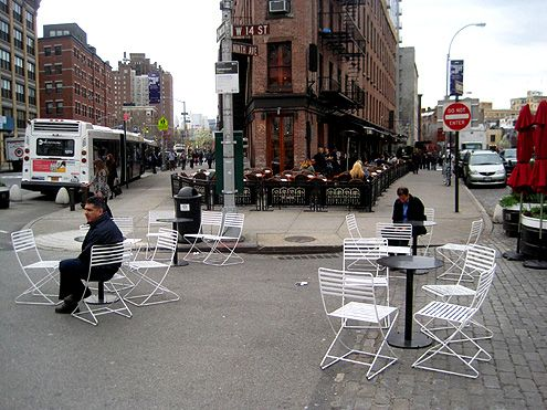 Tables and chairs sit beyond the curb on what was once a very wide intersection