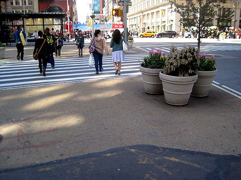 Inexpensive paint and planters are used to create this large and very pedestrian friendly bump out to shorten the distance it takes to cross a street