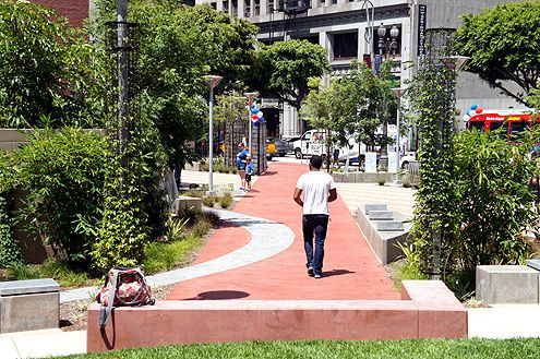An adobe colored pathway leads pedestrians into and out of the park