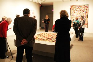 On Member Preview Day, visitors examine quilts on a tour led by Associate Curator Virginia Treanor