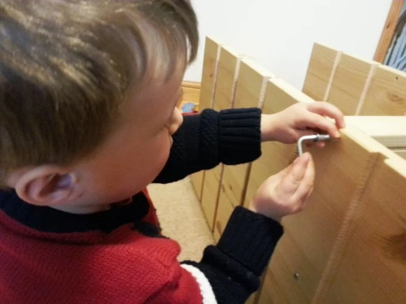 toddler making flat pack furniture