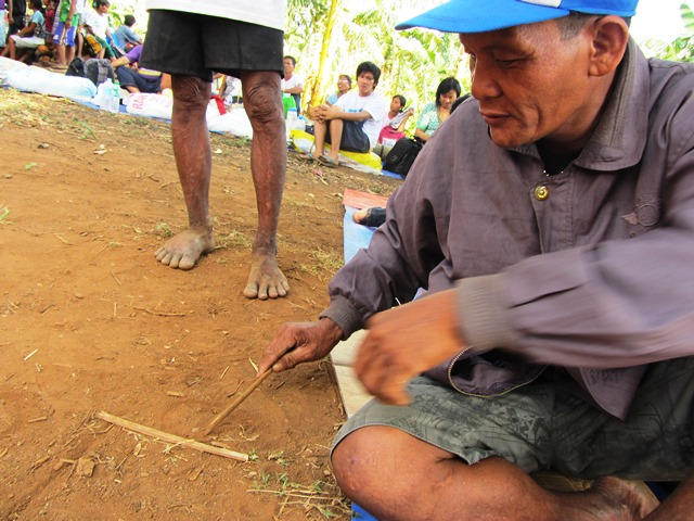 Mangyan leader Altang Dawseg sketches on the ground how a dam being  constructed in their village would submerge  farms and isolate the upland Mangyan. (Apr 2013 Photo by M. Salamat / www.bulatlat.com)
