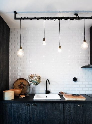 black and white industrial kitchen lighting Stained black Ikea cabinets contrast with the white subway tile Photograph by Anna Kern for