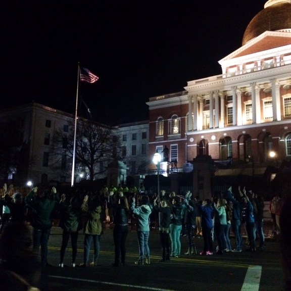 Protesters gathered in a circle in front of the State House. | Photo by Andrea van Grinsven