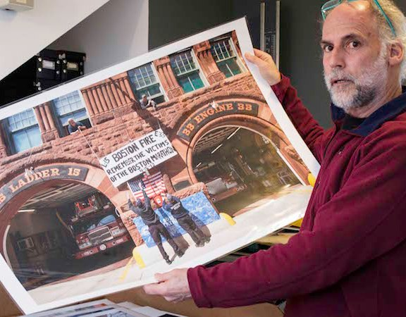 Touster holds up print of a photo he took at the Boston Fire Department's Engine 33 & Ladder location on Boylston Street just blocks from where the bombs went off. The firehouse raised a sign in memory of the victims of the 2013 Boston Marathon bombings.