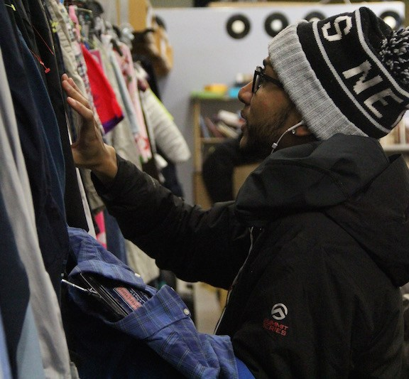 Reinaldo Santana, 23, of Boston, looks through shirts at The Goodwill at 965 Commonwealth Avenue. Santana found a name brand product, a Vineyard Vines button-down, for a fraction of its retail cost.