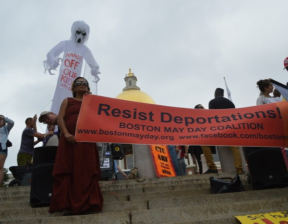 "Jamie McLaughlin of the Boston May Day Coalition holds a ""Resist Deportations"" banner before the rally."