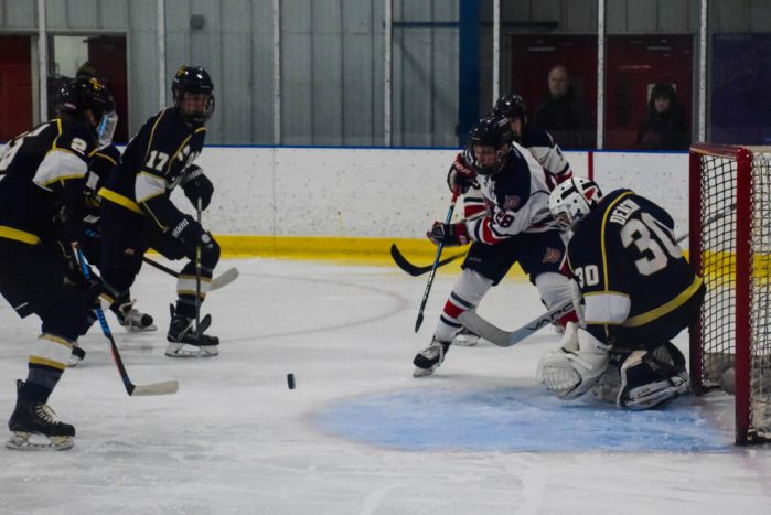 Tim Freed (28) attempts to play a puck in front of John Carroll's goal.