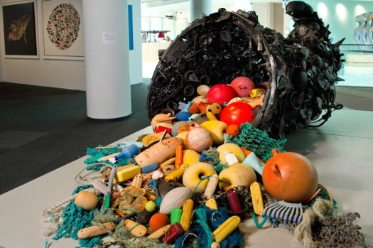 Pam Longobardi, Bounty, Pilfered, 2014, salvaged ocean plastic; photographs by Susan Middleton are on the back wall.