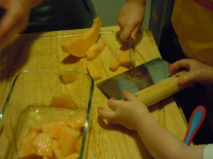 Bl using the bench scraper to scoop up the melon pieces