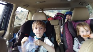 all 3 kids eating and listening to podcast in car