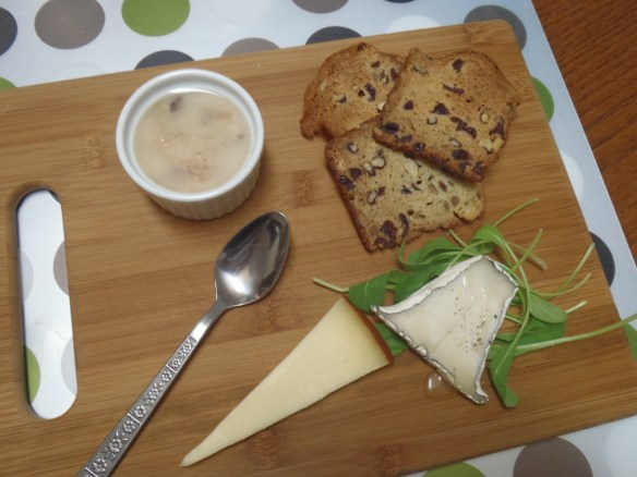 A tasting board: potted rabbit, dried fruit crackers, Smoky Valley Valencay with honey and black pepper, and Sylvan Star mild gouda