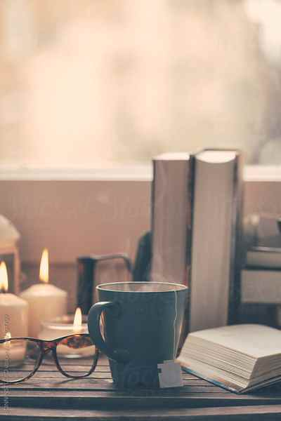 Still life of used books, tea, glasses and candles on a ...