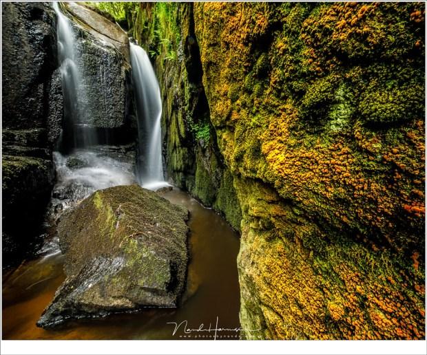 Verborgen tussen rotsen en achter rotsen, een intieme waterval van meters hoog.