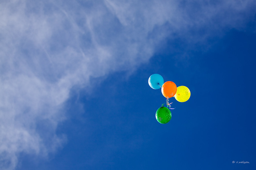 4 helium balloons floating up into a deep blue sky Flickr