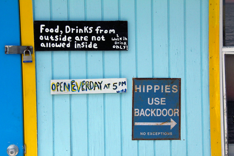 Sign: Hippies use backdoor; No Exception; Old sign informing Hippies to use the backdoor at a bar on Green Turtle Cay, Bahamas.
