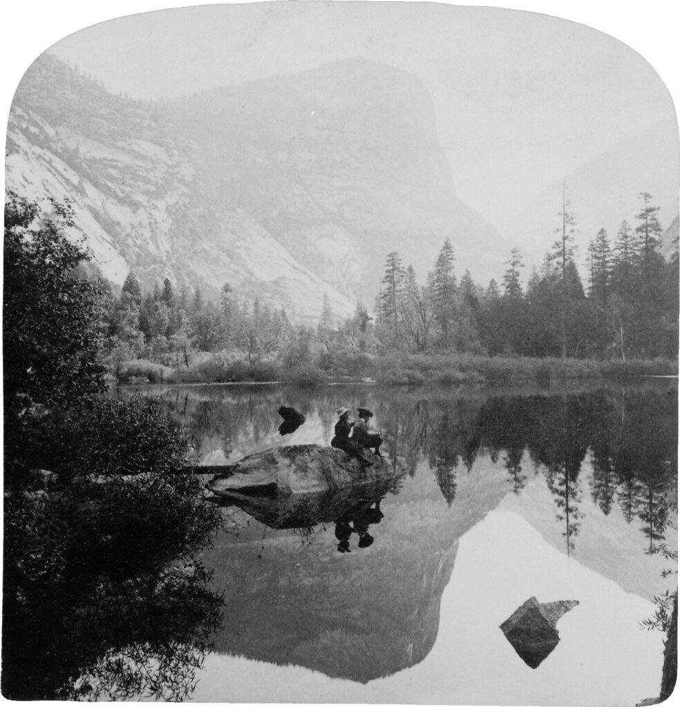 Two women sitting on rock in middle of mirror-smooth lake. Mirror Lake, where nature multiplies her charms—looking (N.E.) to Mt. Watkins, Yosemite Valley, California (1902)