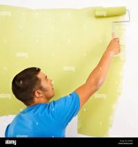 Man painting over white wall with green paint using paint ...