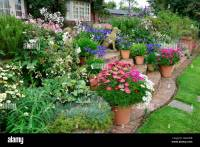 Colourful garden terrace with mixed flower beds and ...