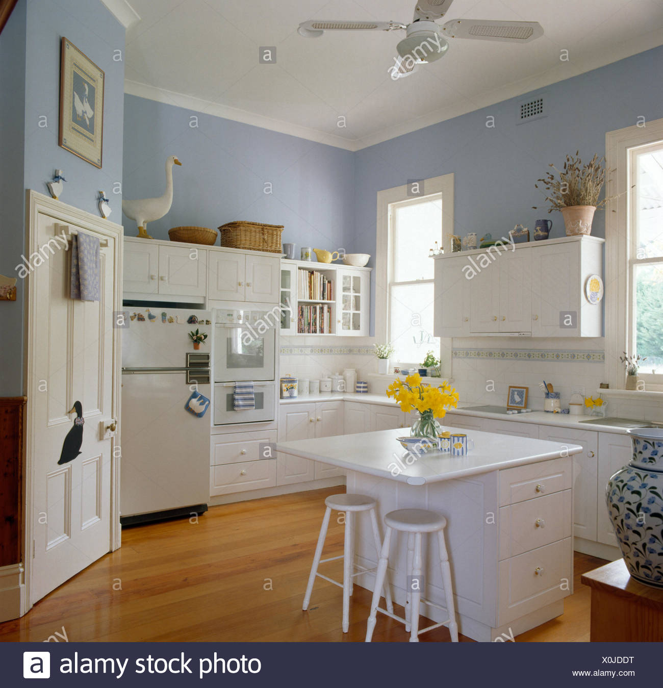 Pale Blue Kitchen White Stools At Island Unit In A Pale Blue Kitchen With Wooden