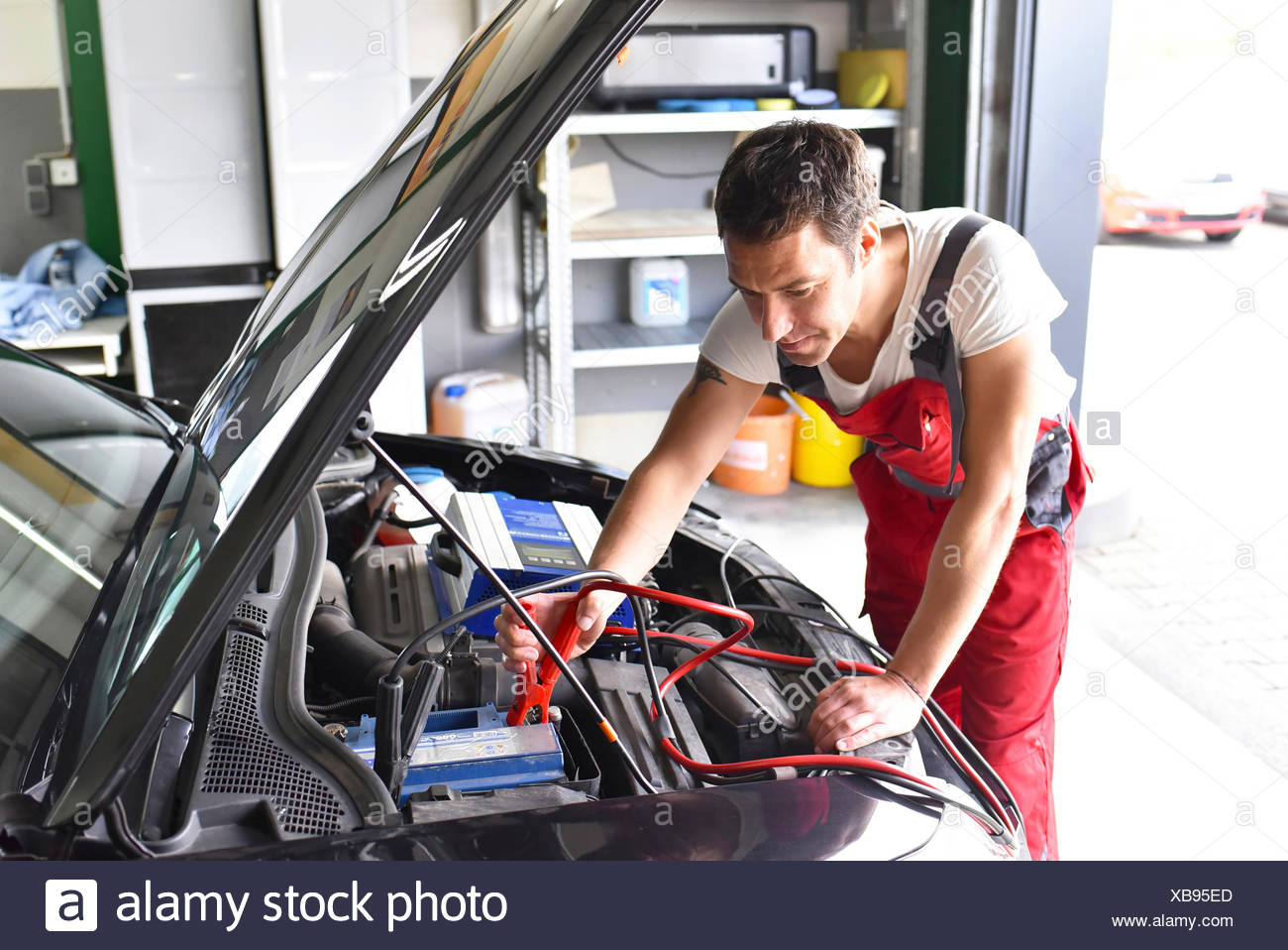 Garage Auto 95 Car Mechanic Working In Repair Garage Reloading Car Battery Stock