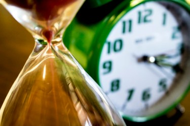 hourglass in the foreground and a clock in the background