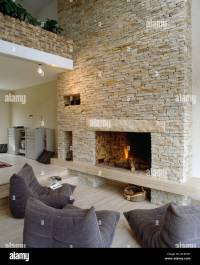 Lit fire in fireplace in stone wall of barn conversion ...