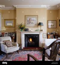 English country style living room with mantel piece, arm ...