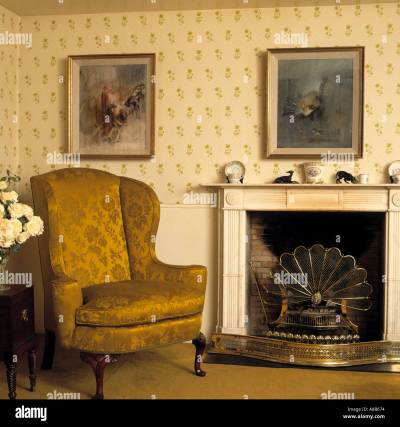 Gold brocade armchair beside fireplace with fan-shaped fireguard in Stock Photo: 570996 - Alamy