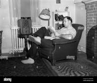 1950s MAN SITTING IN CHAIR IN LIVING ROOM SMOKING PIPE ...