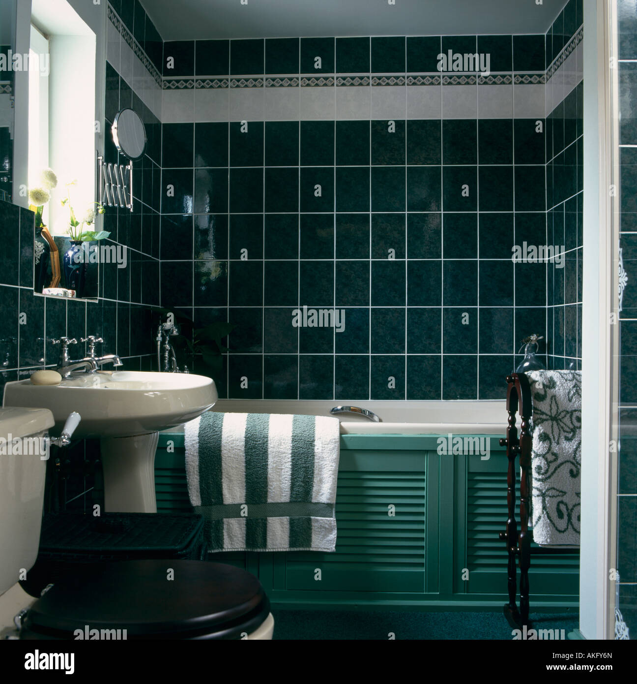 Green Striped Towel On White Bath With Green Panelling In Bathroom Stock Photo Alamy