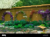 Tall wood fence with vines by flower garden rock path and ...