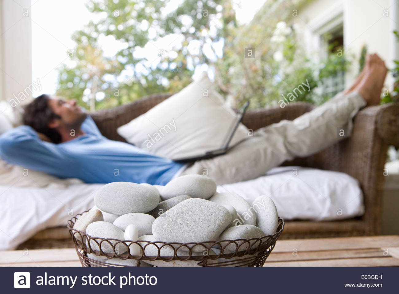 Laptop Tisch Sofa Pebbles In Bowl On Table Man Lying On Sofa With Laptop On Lap In
