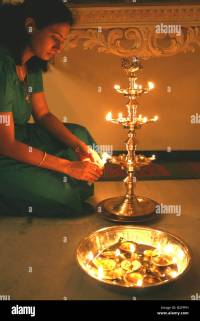 Woman lights a large Hindu oil lamp on the occasion of ...