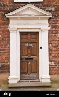 Brown wooden front door with white frame and pediment on ...