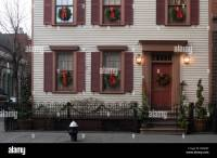 Shuttered windows with Christmas wreaths adorn the facade ...