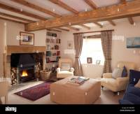 country style living room with lit open fire and cream ...
