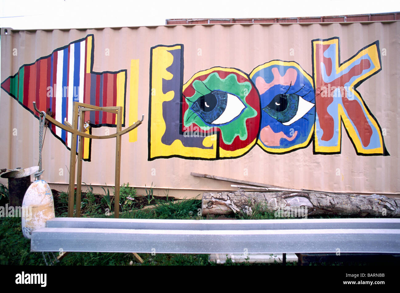 Colorful look graffiti art information sign with arrow pointing in left direction painted on exterior side