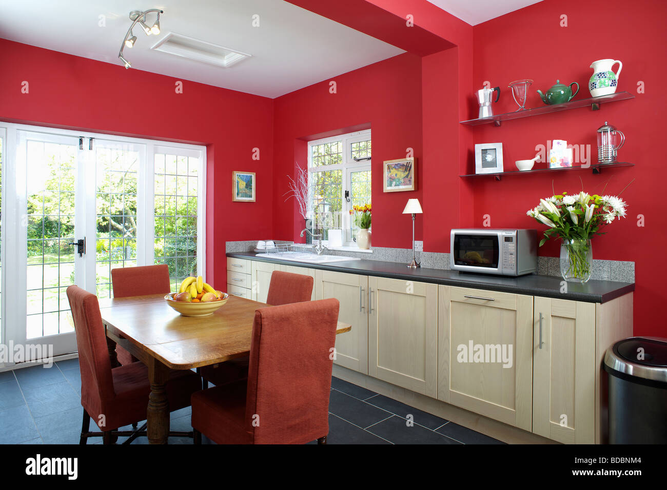 wood table and red upholstered chairs in red kitchen dining room extension BDBNM4