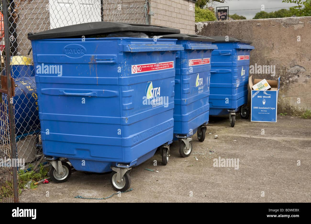 Three Large Blue Plastic Commercial Wheelie Bins Full Of