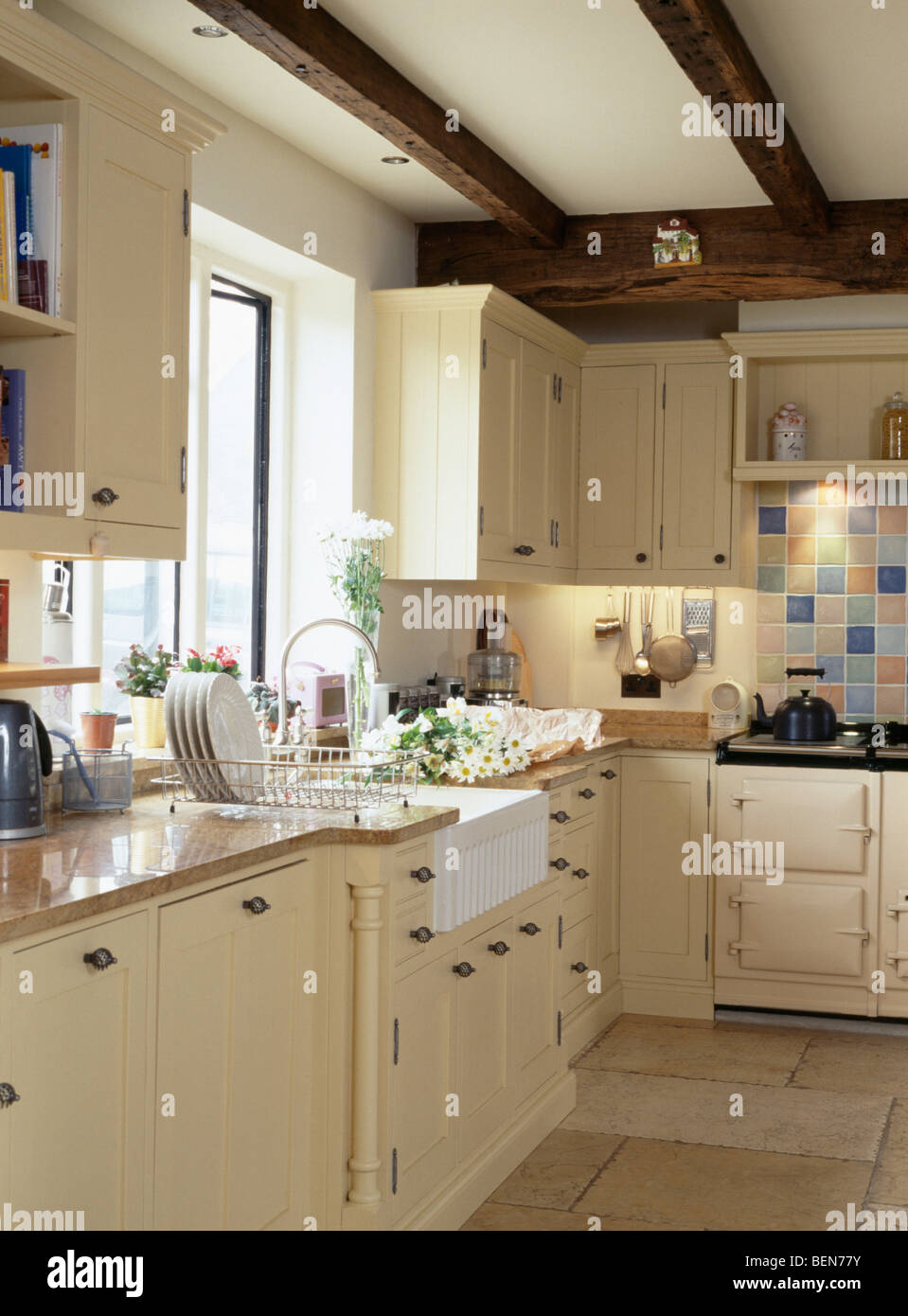 Belfast sink below window in country cottage kitchen with cream fitted units