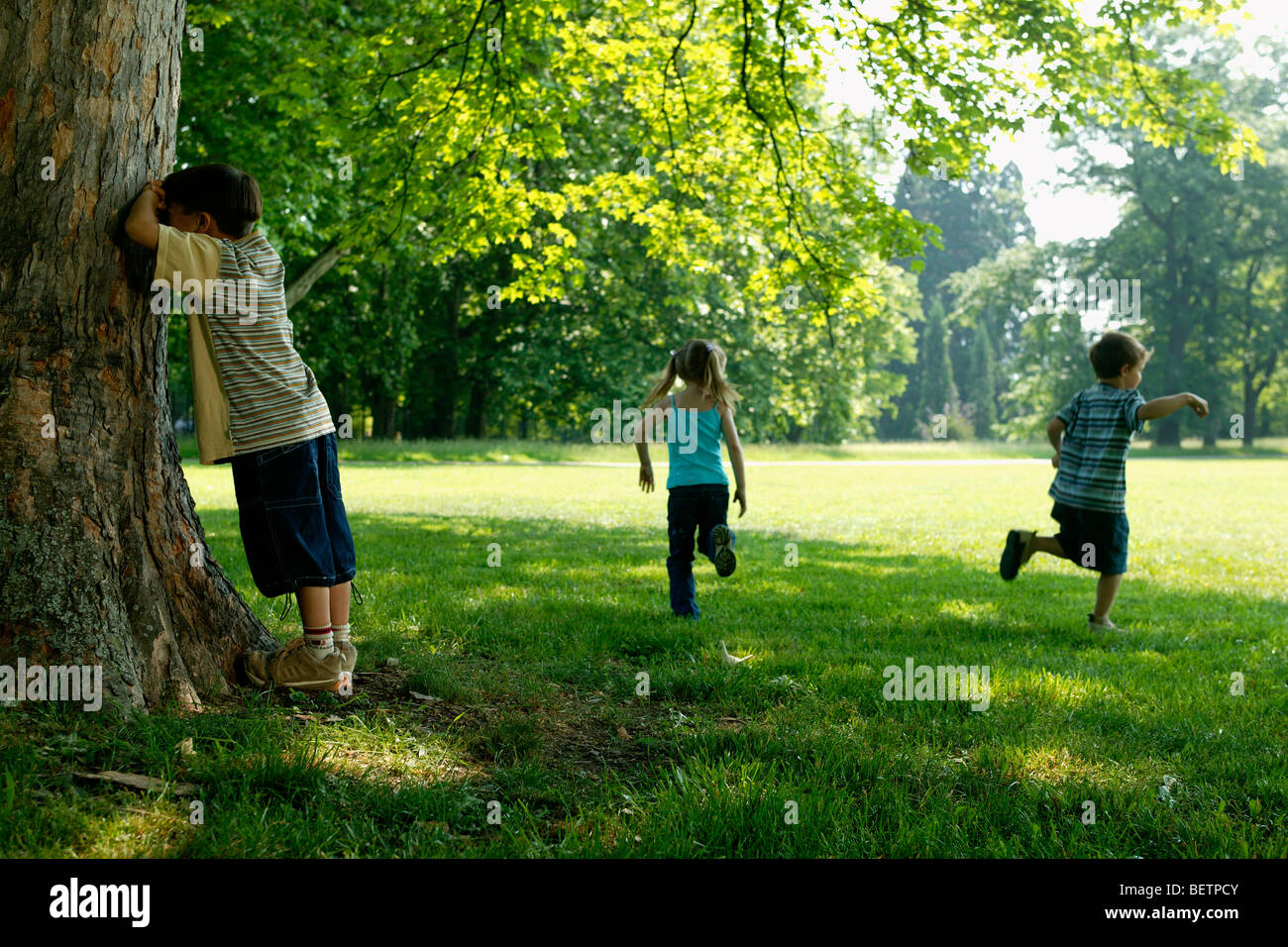 Hide And Seek Kids Three Children Playing Hide And Seek In The Park Stock Photo