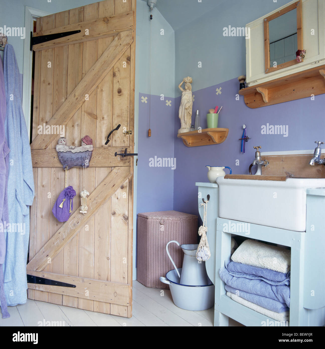 Stock photo stripped pine door in cottage bathroom with two tone painted blue walls and large white basin in pale blue vanity unit