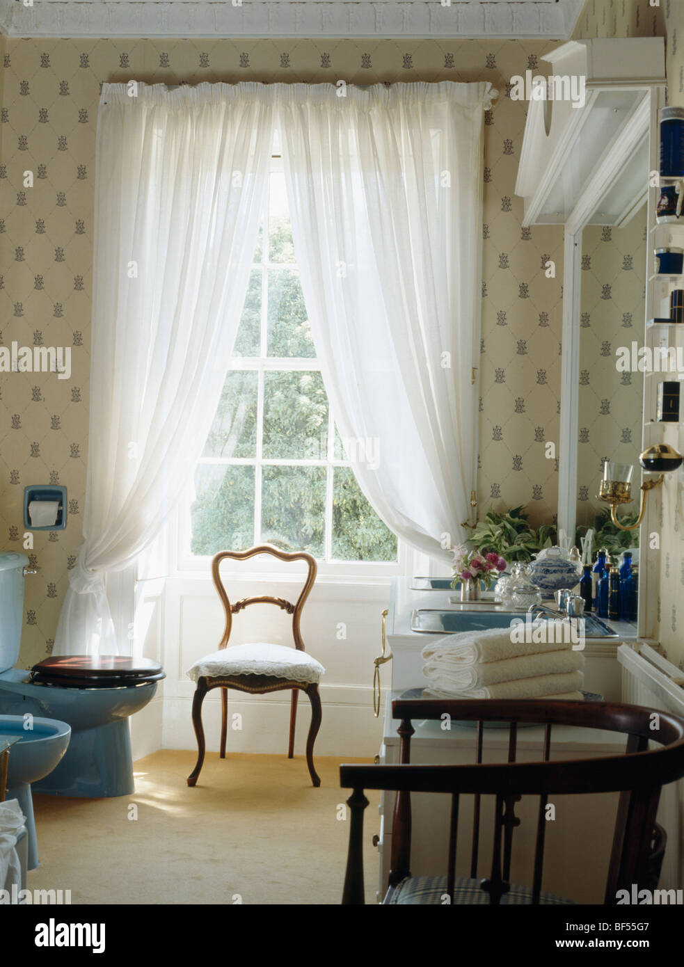 Antique chair in front of tall window with white voile