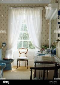 Antique chair in front of tall window with white voile ...