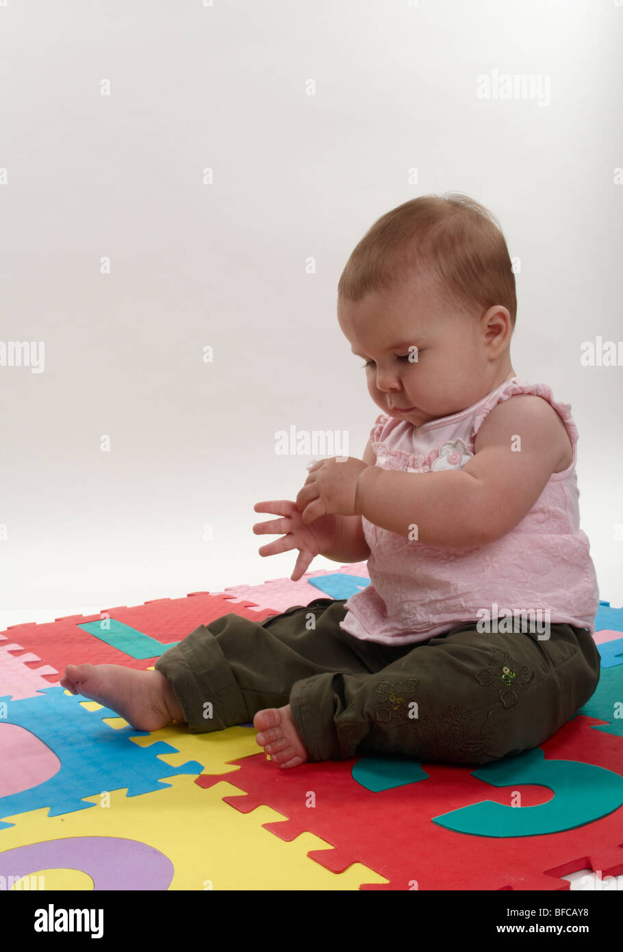 Baby 12 Monate 12 Month Old Baby Girl Playing On Floor In Pink Stock Photo - Alamy