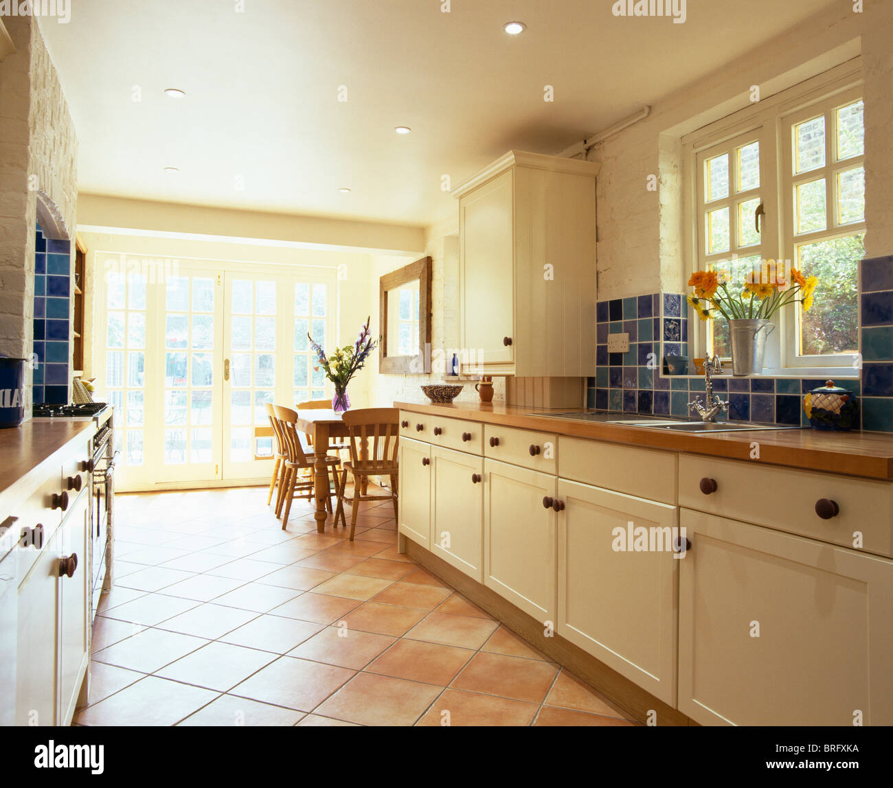 Terracotta tiled floor in open plan kitchen dining room extension with cream fitted units