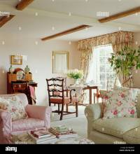 Pink floral cushions on pink armchair and pale green sofa ...