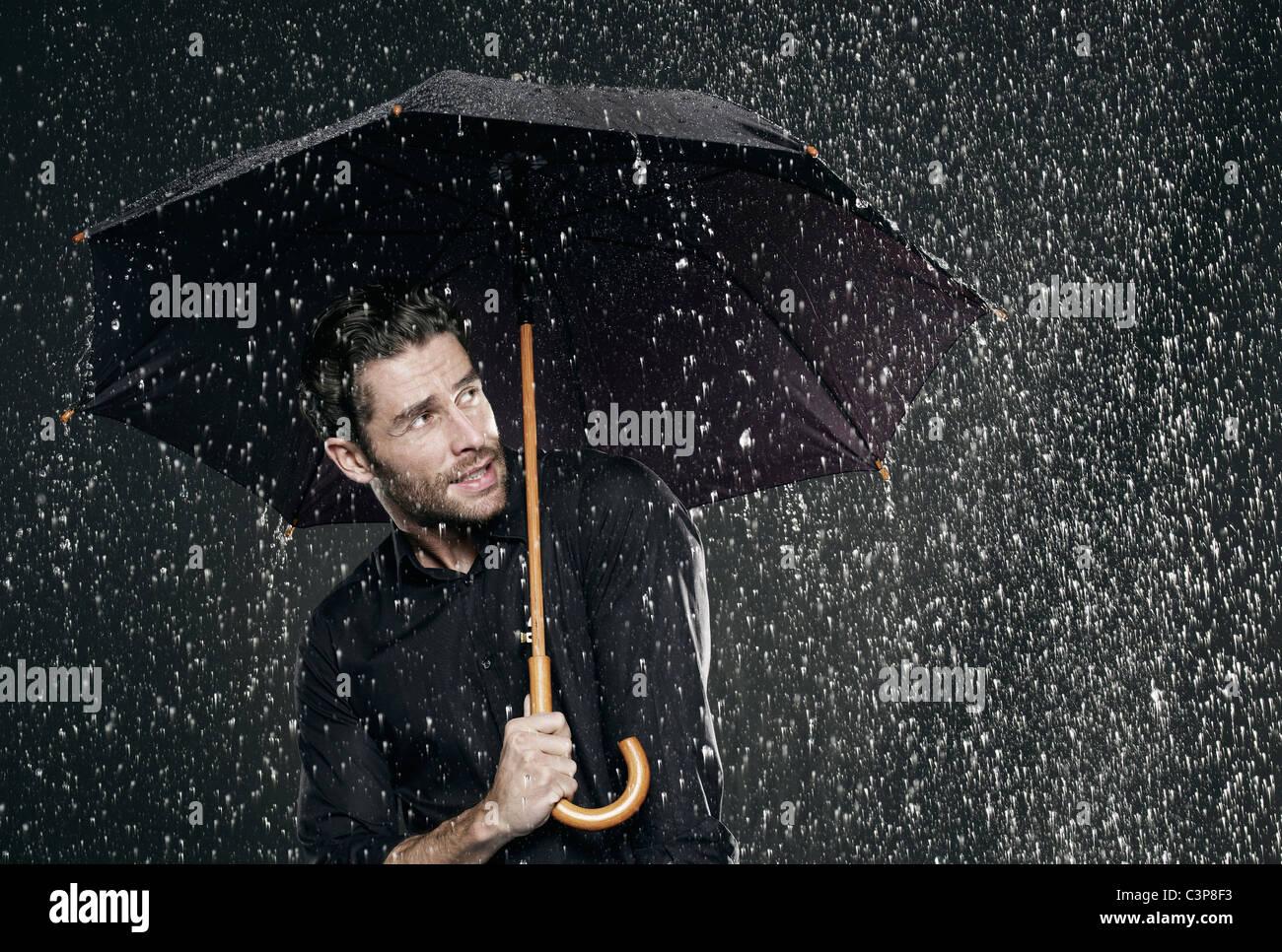 Rain Drop Wallpaper Hd Man Holding Umbrella In Rain Looking Away Stock Photo
